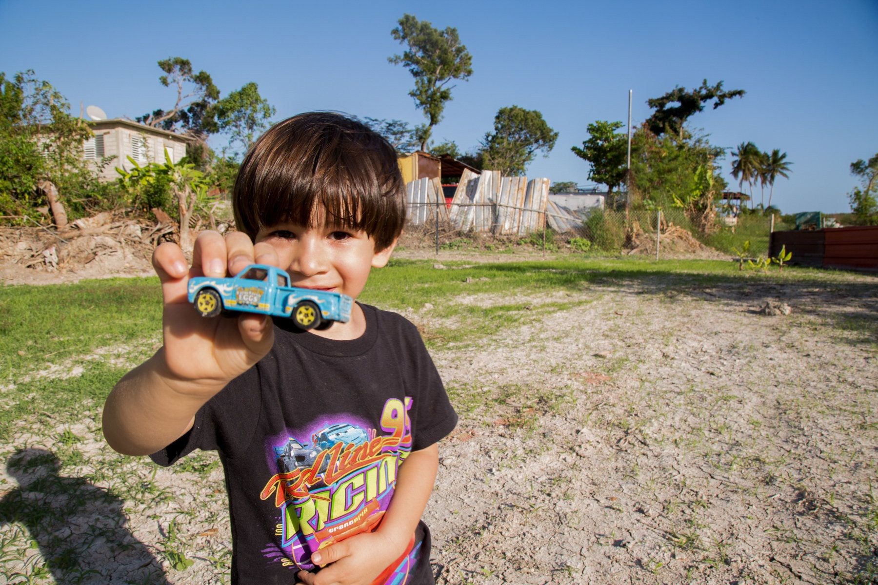 A 4-year old boy plays with his toy truck in the backyard of his home in Peñuelas. His house was flooded by coal ash f