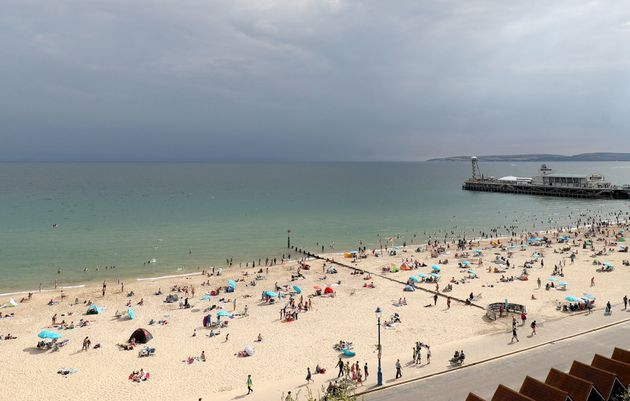Storm clouds gather out at sea as people enjoy the warm weather on Bournemouth beach on