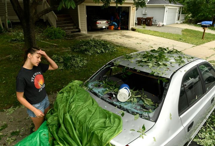 Sara Pilot, left, looks at the hail damage to her father's car outside of her home in Louisville, Colorado, on June 19.