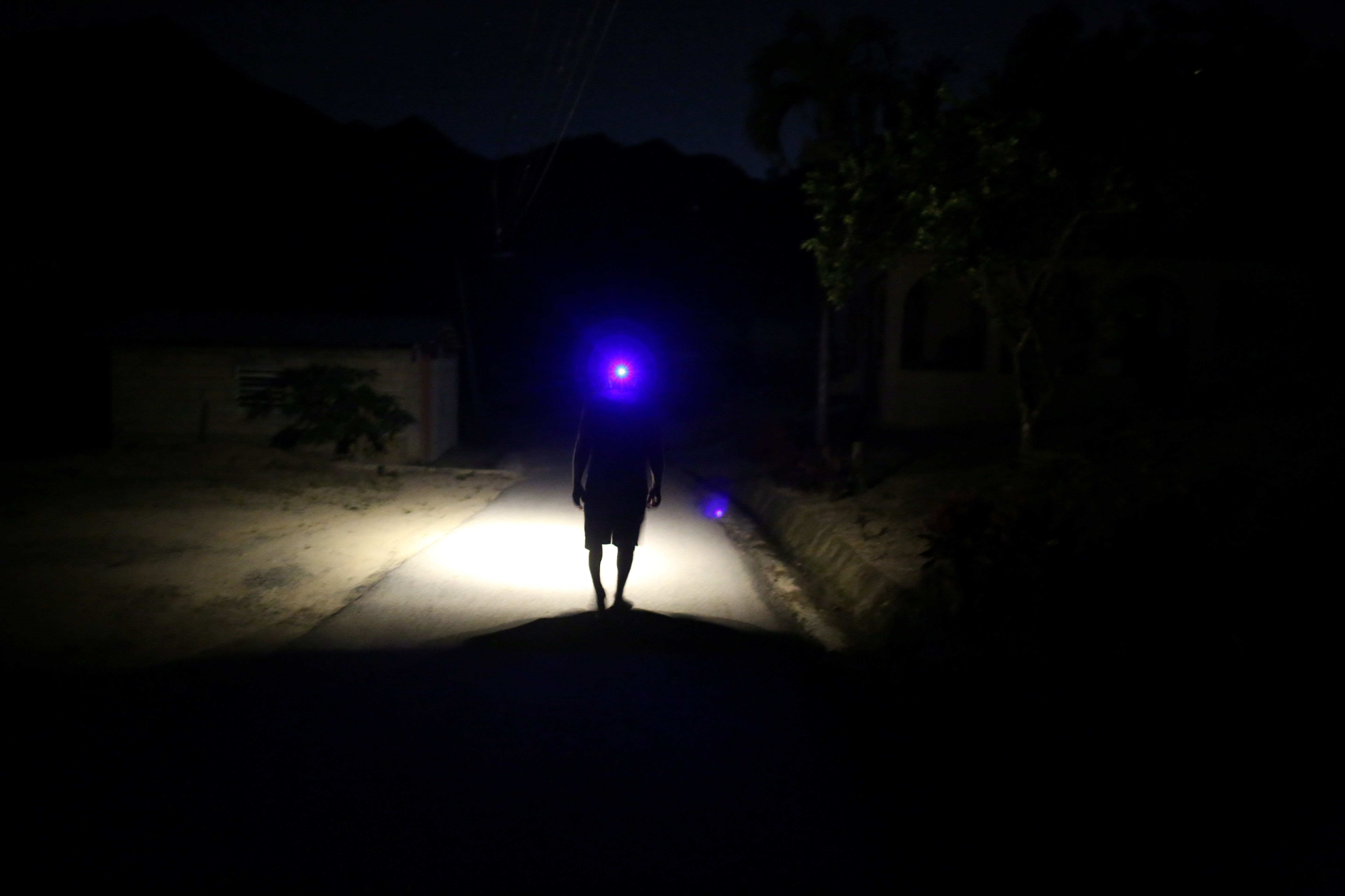 Jose Alvarez, 60, uses a head lamp while walking in the dark as the island's fragile power system is still reeling from the devastation wrought by Hurricane Maria eight months ago, in Jayuya, Puerto Rico May 10, 2018. Picture taken May 10, 2018. REUTERS/Alvin Baez