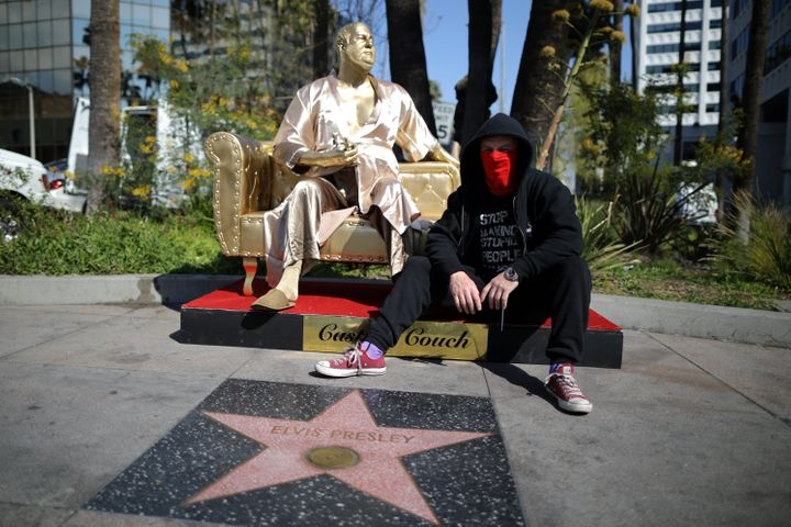 Artist Plastic Jesus sits on his statue of Harvey Weinstein on a casting couch on Hollywood Boulevard in Los Angeles.