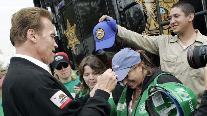 Former Republican California Gov. Arnold Schwarzenegger signs the cap of a Community Emergency Response Teams (CERT) member a