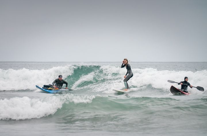 High Fives Athletes share a wave in San Clemente during an adaptive surf camp in 2017.