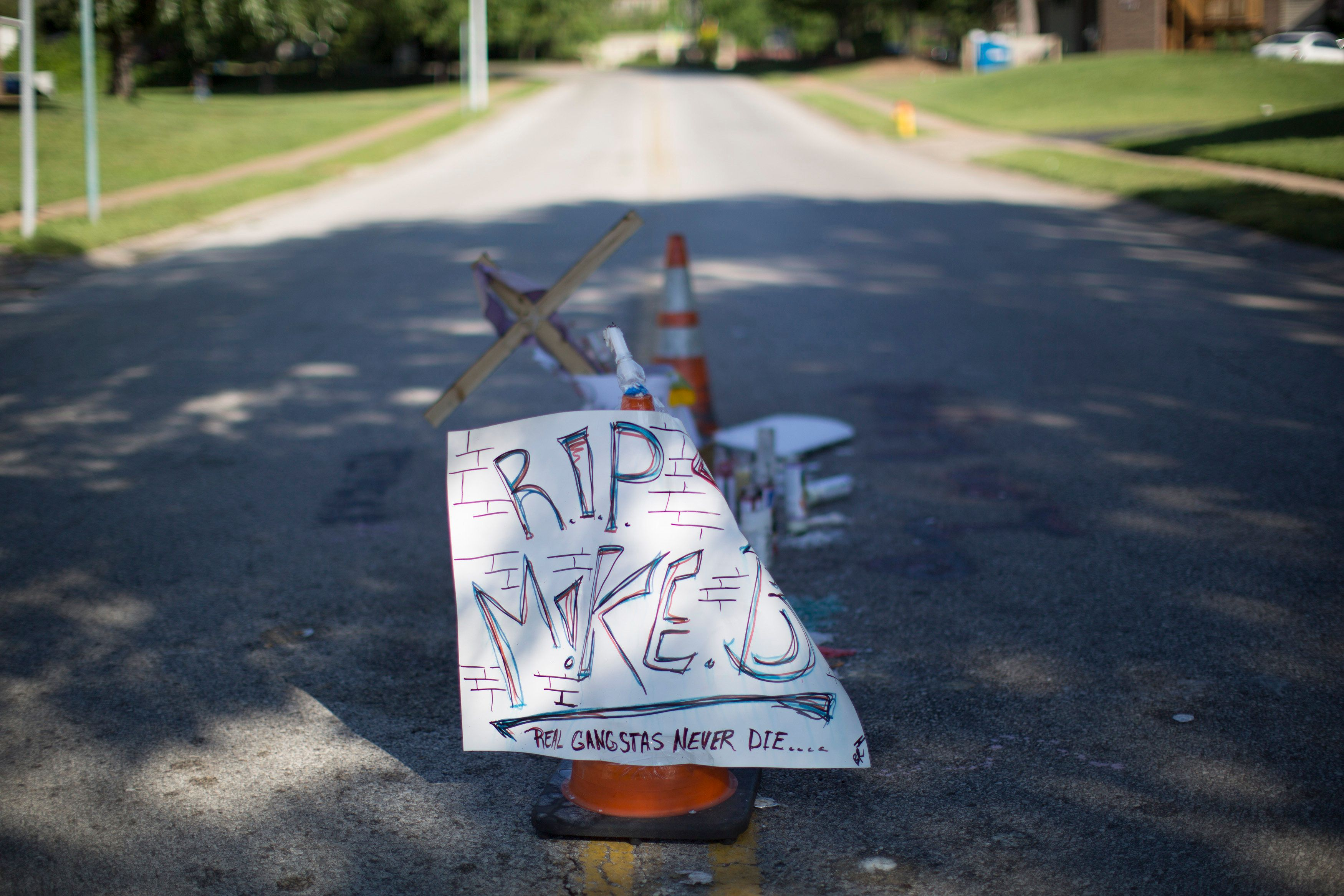 A makeshift memorial is pictured where black teenager Michael Brown was shot to death by police over the weekend in Ferguson, Missouri August 12, 2014. Police said Brown, 18, was shot in a struggle with a gun in a police car but have not said why Brown was in the car. At least one shot was fired during the struggle and then the officer fired more shots before leaving the car, police said. But a witness to the shooting interviewed on local media has said that Brown had been putting his hands up to surrender when he was killed. The FBI has opened a civil rights investigation into the racially charged case and St. Louis County also is investigating. REUTERS/Mario Anzuoni (UNITED STATES - Tags: CRIME LAW)