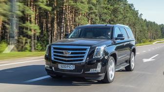 Minsk, Belarus - August 1, 2017: Cadillac Escalade drives on a road during a sunny day. Cadillac Escalade is a luxury SUV and a first light truck in the history of the Cadillac brand. Under the hood, there's a 6.2-litre V8 developing 420 horsepower and an impressive 623 Nm of torque.