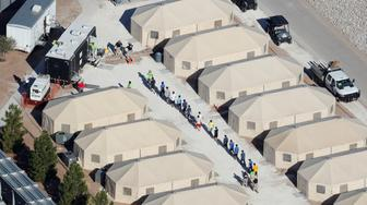 "Immigrant children now housed in a tent encampment under the new ""zero tolerance"" policy by the Trump administration are shown walking in single file at the facility near the Mexican border in Tornillo, Texas, U.S. June 19, 2018.        REUTERS/Mike Blake       TPX IMAGES OF THE DAY"