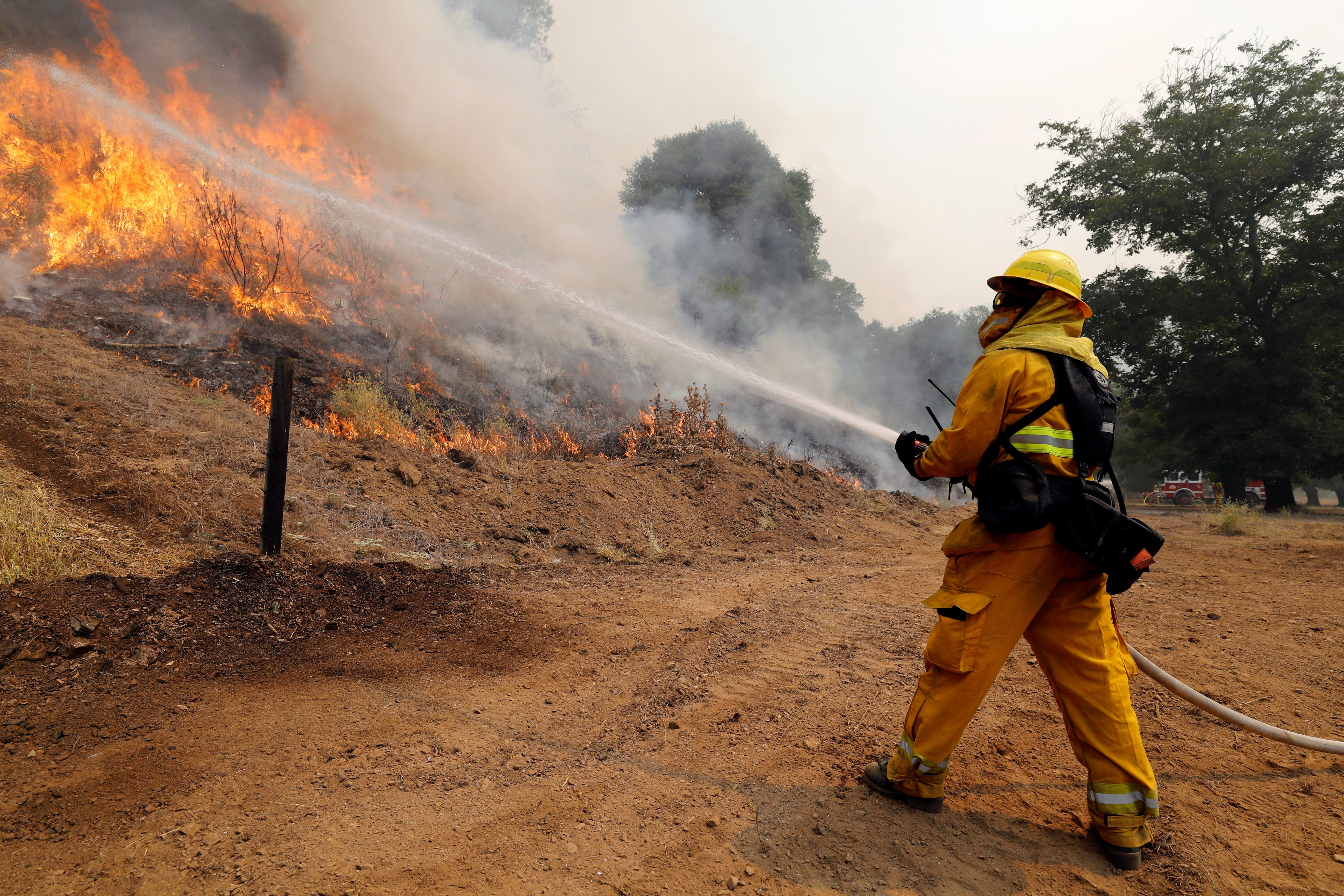 A firefighter uses a hose to knock down flames from the Ranch fire (part of the Mendocino Complex fire) north of Upper Lake,