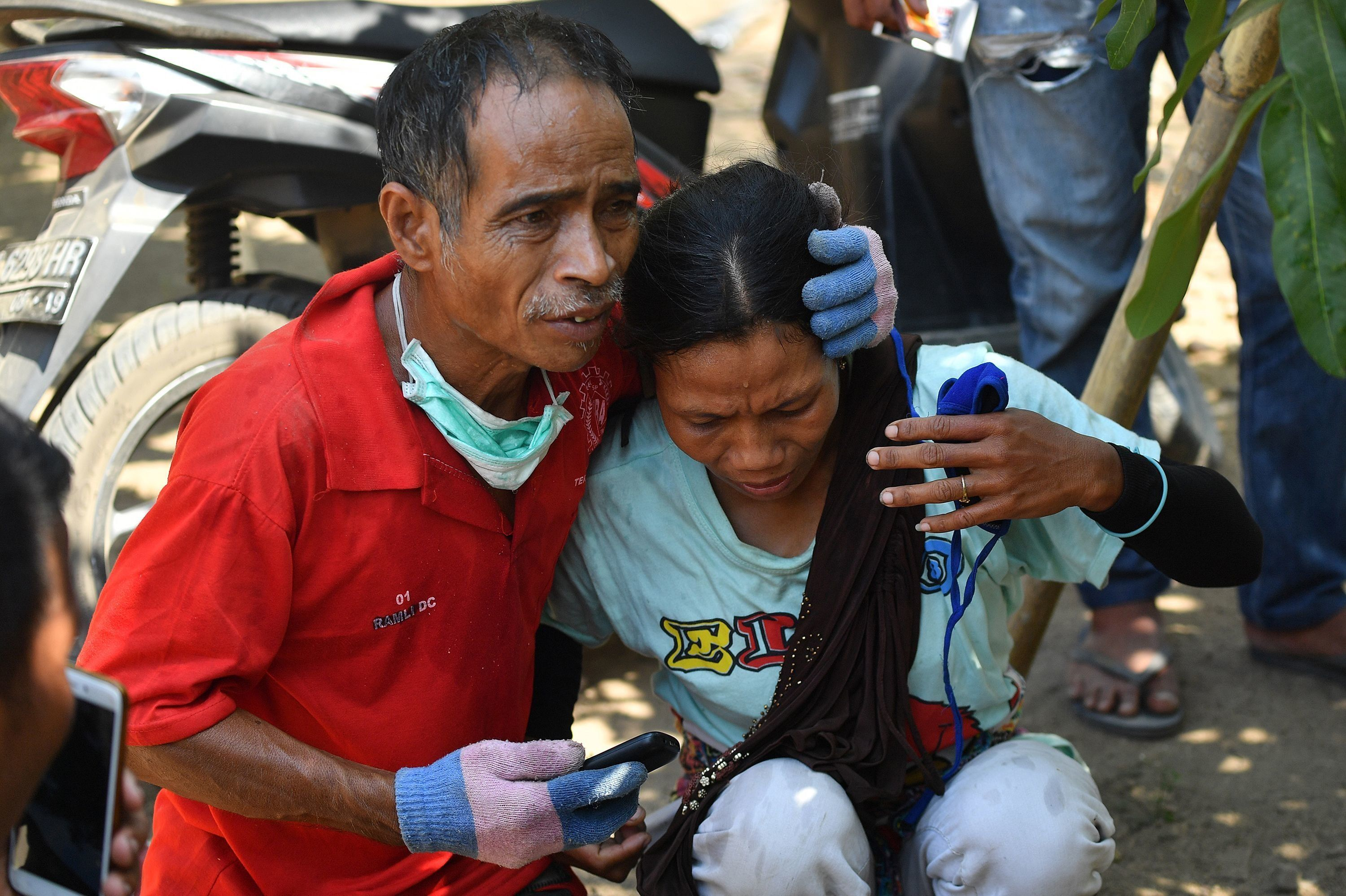 An Indonesian man tries to calm a woman after a strong aftershock hit Lombok island on Thursday.