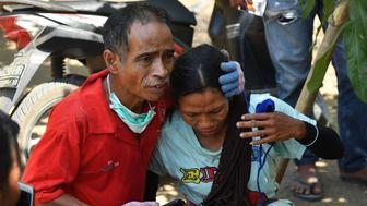 An Indonesian man (L) tries to calm a woman shortly after an aftershock hits the area in Tanjung on Lombok island on August 9, 2018. - A strong aftershock struck Indonesia's Lombok on August 9, causing panic among evacuees sheltering after a devastating earthquake killed more than 160 on the holiday island four days earlier. (Photo by ADEK BERRY / AFP)        (Photo credit should read ADEK BERRY/AFP/Getty Images)