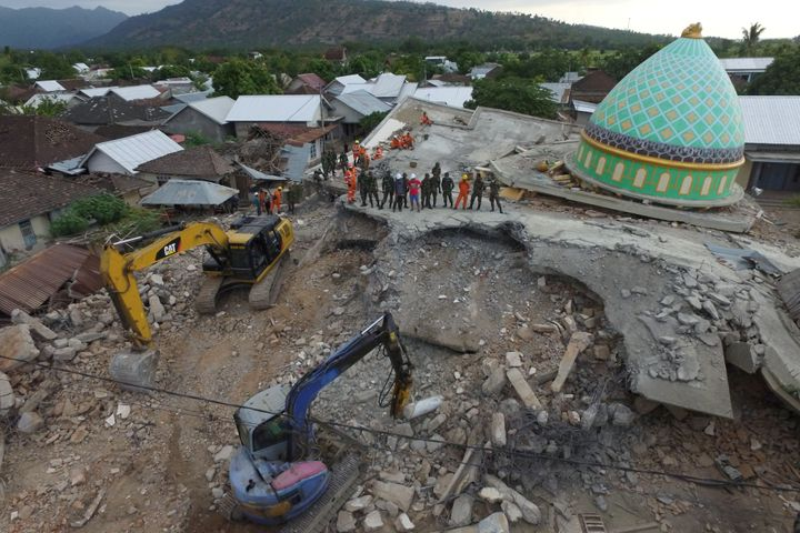 Rescue workers and soldiers search through the rubble for earthquake victims in Lombok, Indonesia.