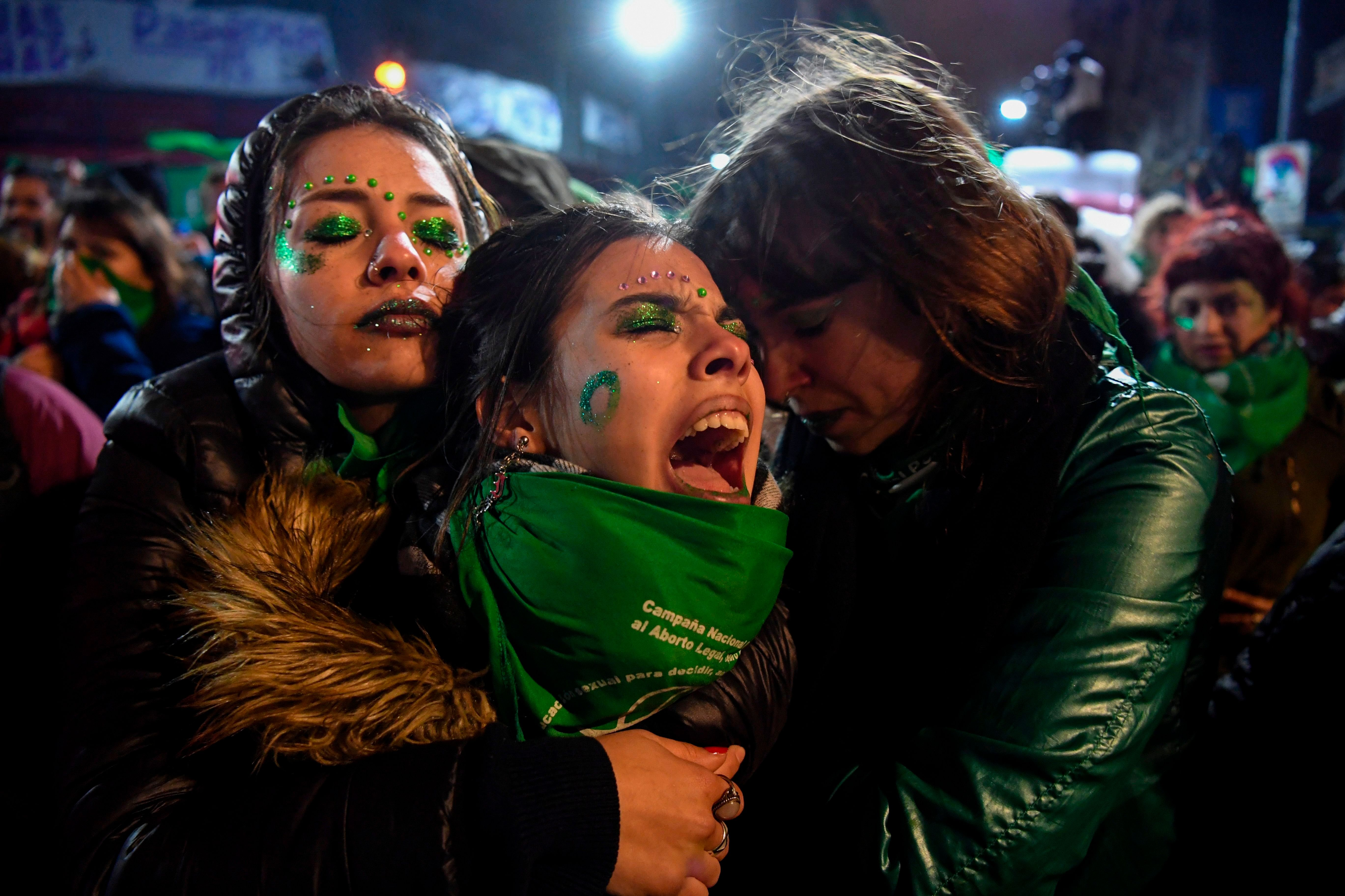 Activists in favour of the legalization of abortion comfort each other outside the National Congress in Buenos Aires, on August 9, 2018 after senators rejected the bill to legalize the abortion. - Argentine senators on Thursday voted against legalizing abortion in the homeland of Pope Francis, dashing the hopes of women's rights groups after the bill was approved by Congress's lower house in June. According to an official tally, 38 senators voted against, 31 in favor, while two abstained. (Photo by EITAN ABRAMOVICH / AFP)        (Photo credit should read EITAN ABRAMOVICH/AFP/Getty Images)