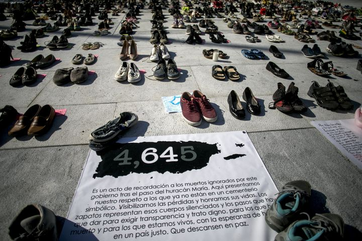 A sign reads '4,645' near empty pairs of shoes outside San Juan's Capitol building during a June protest against the governme