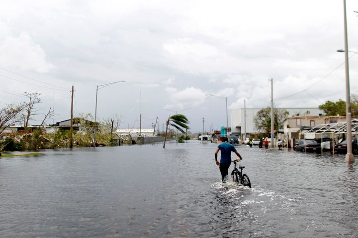 A man wades on the water while pushing his bicycle through a flooded street in the aftermath of Hurricane Maria in Catano, Pu