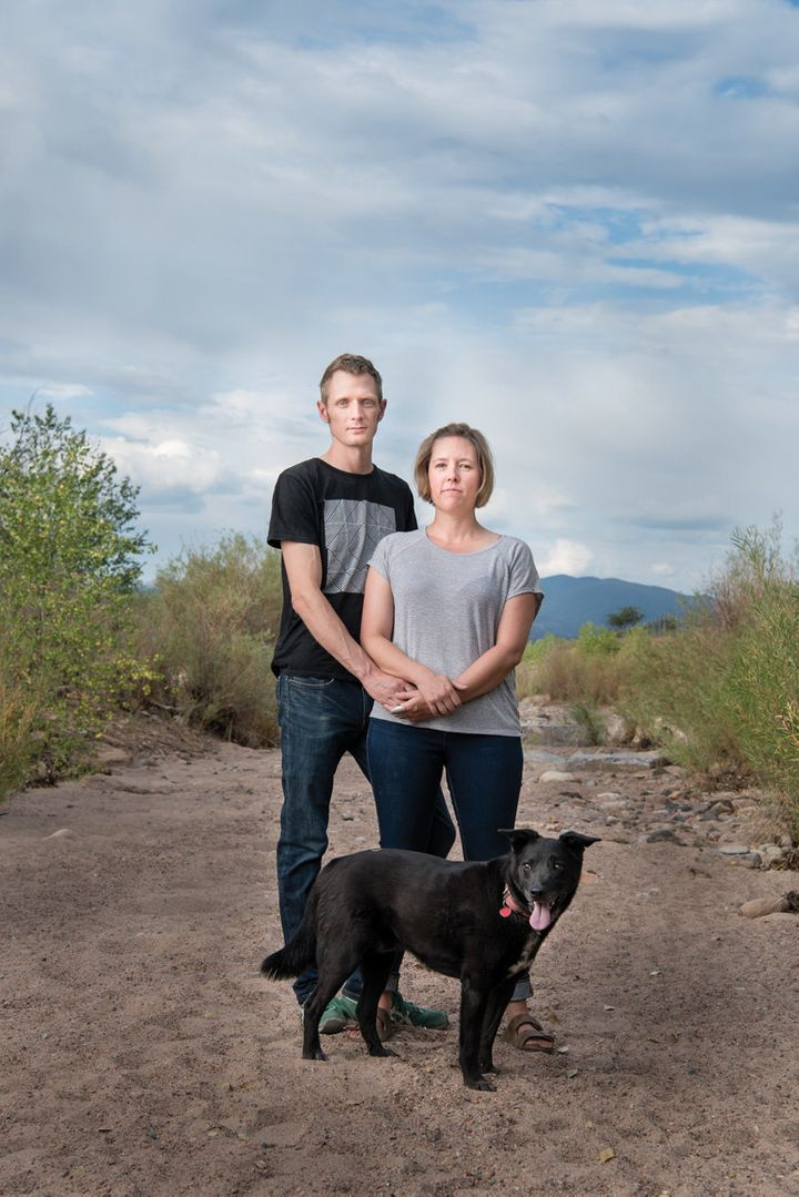 Colin Dyck and author Cally Carswell stand with their dog, Google, in the dry Santa Fe riverbed near their home in Santa Fe,