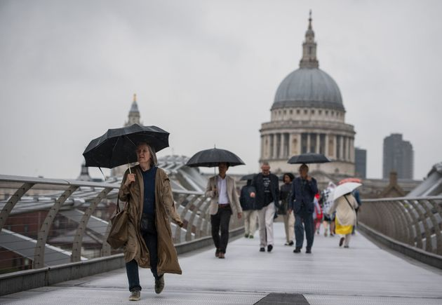 People shelter under umbrellas as they cross the Millennium Bridge, London, as rain brings an end to the recent spell of hot weather.