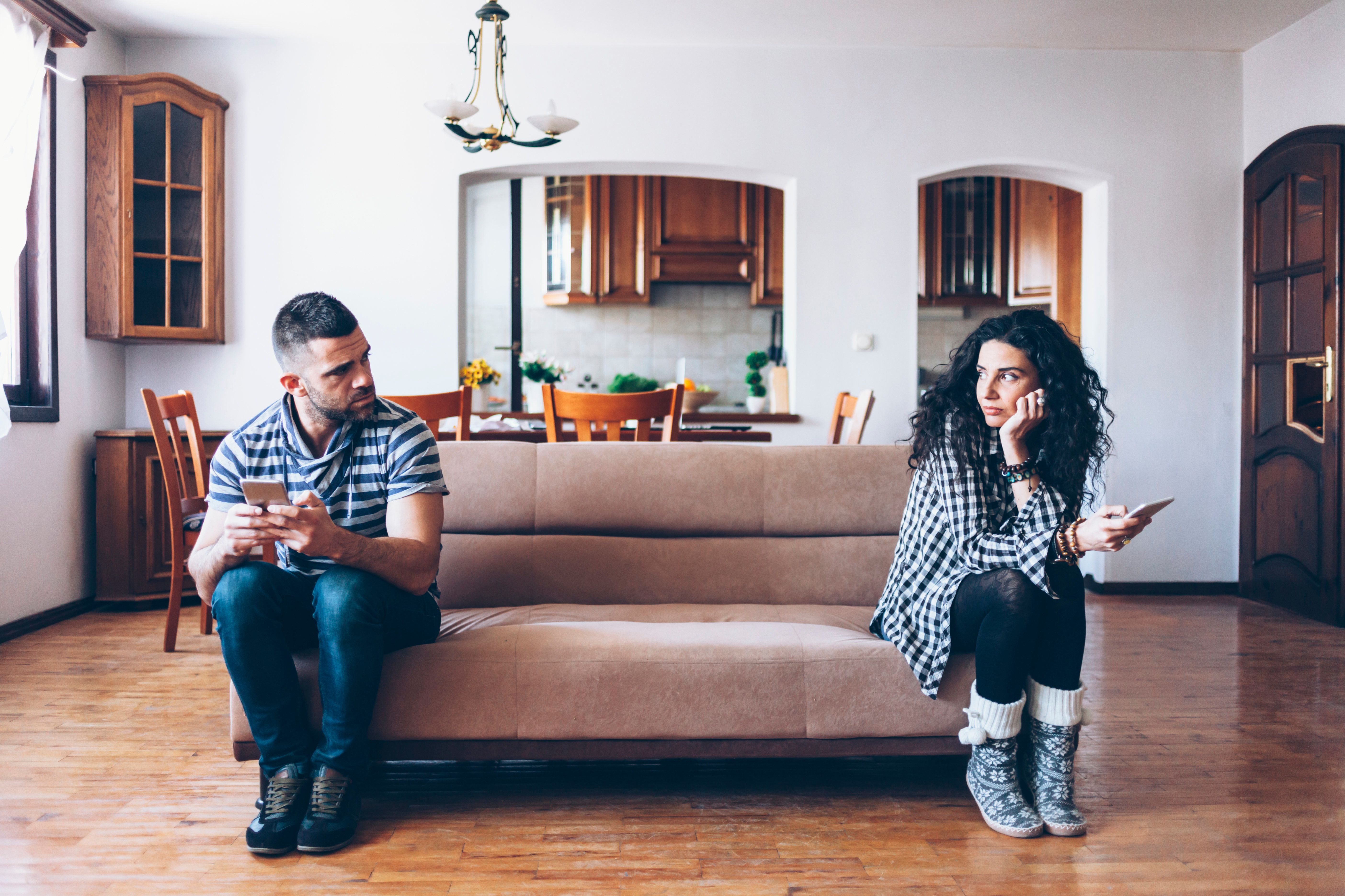 Couple in conflict sitting on sofa at home, using smart phones.