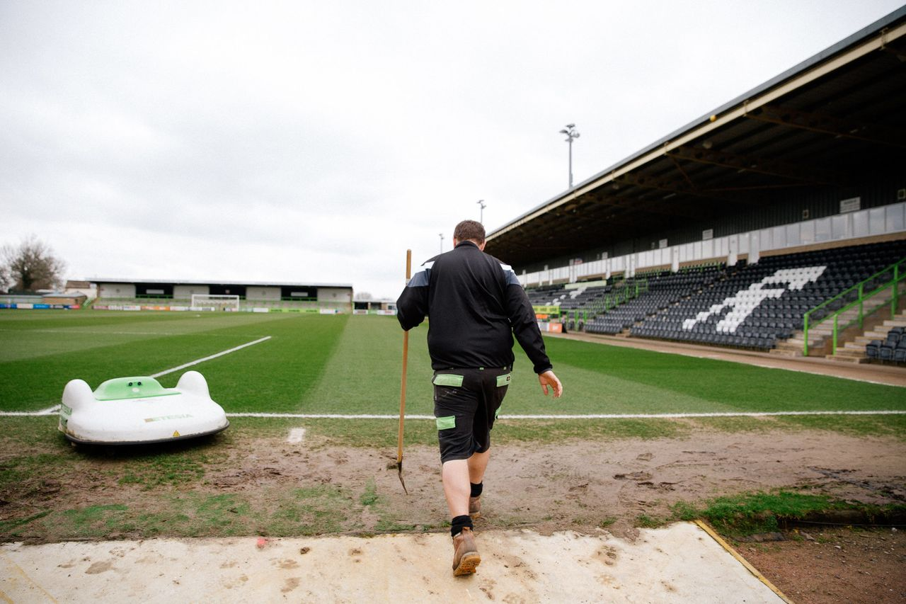 """Groundsman Adam Witchell and the solar powered """"mowbot"""" that cuts the grass at Forest Green Rover's stadium."""