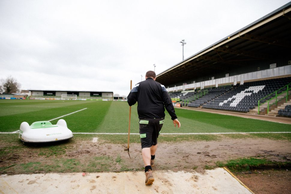 "Groundsman Adam Witchell and the solar powered ""mowbot"" that cuts the grass at Forest Green Rover's stadium."