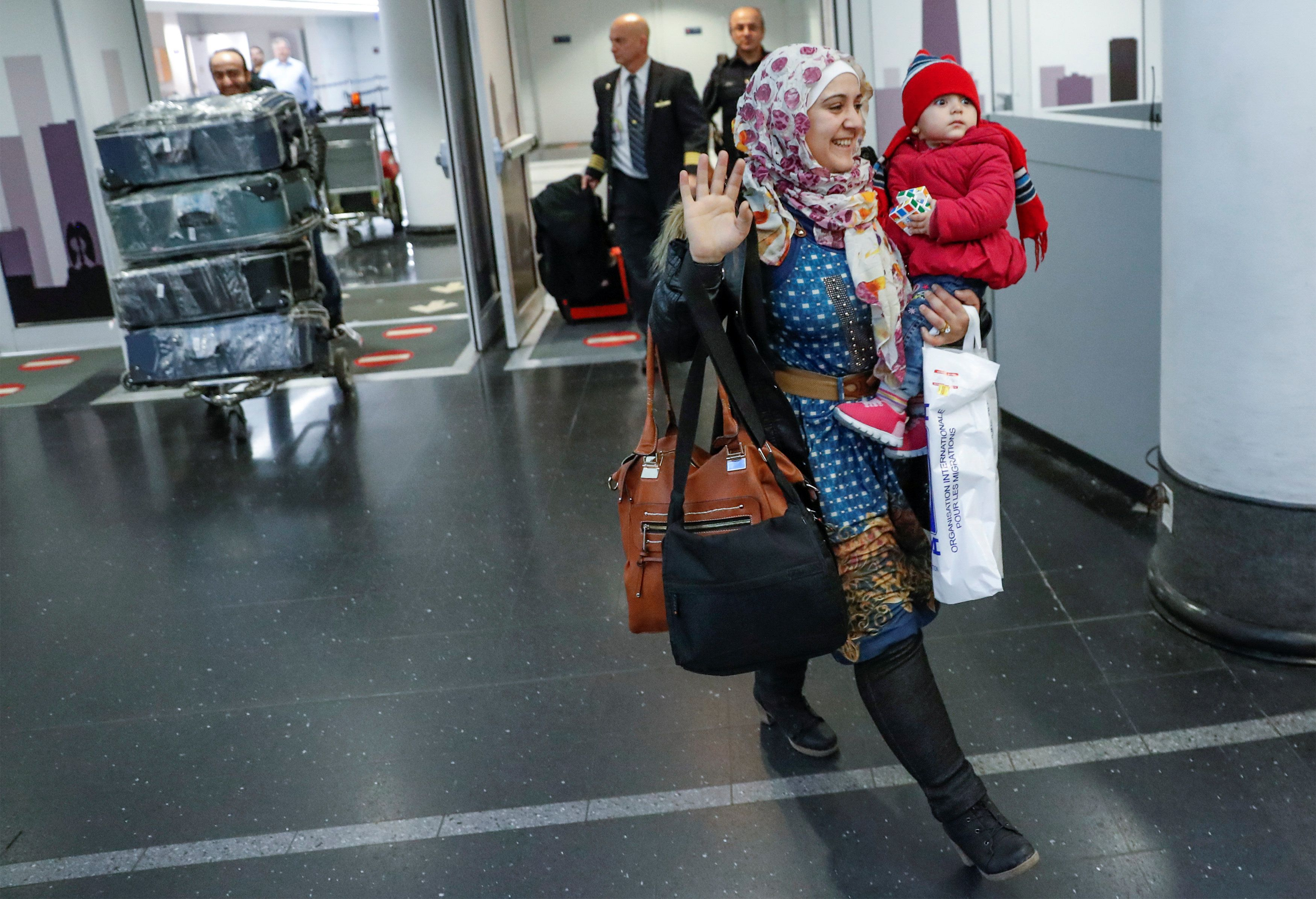 Syrian refugee Baraa Haj Khalaf, her daughter Shams, 1, and husband Abdulmajeed arrive at O'Hare International Airport in Chi