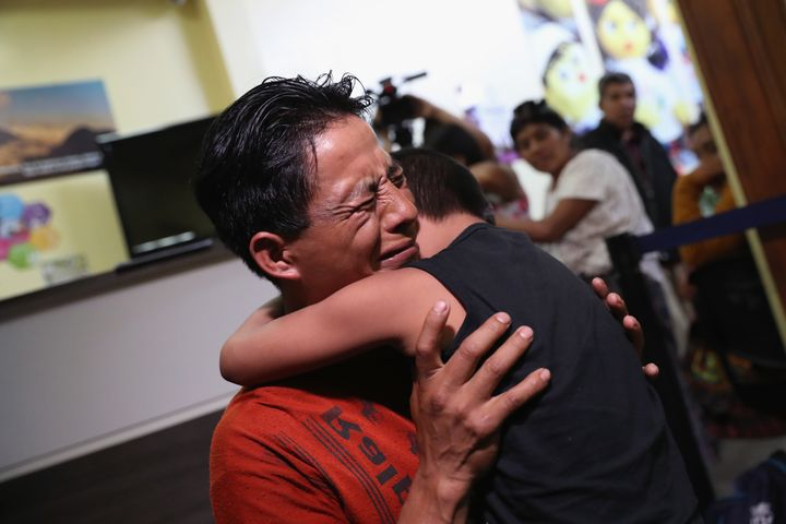 An emotional father embraces his son for the first time in months on Aug. 7, 2018, in Guatemala City, after nine children wer