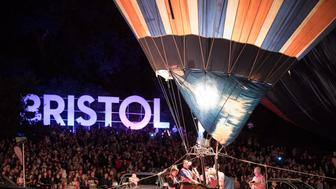 BRISTOL, ENGLAND - AUGUST 9:  Crowds watch as tethered balloons are illuminated by their burners during the night glow evening event on the first day of the Bristol International Balloon Fiesta at the Ashton Court estate on August 9, 2018 in Bristol, England. Now in its 40th year, the Bristol International Balloon Fiesta is one of Europe's largest annual hot air balloon events, hosted in the city that is seen by many balloonists as the home of modern ballooning. (Photo by Matt Cardy/Getty Images)