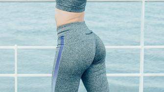 Young attractive woman wearing sportswear, exercising, turning round, looking at camera, stretching arms and standing with river in background. Back view.