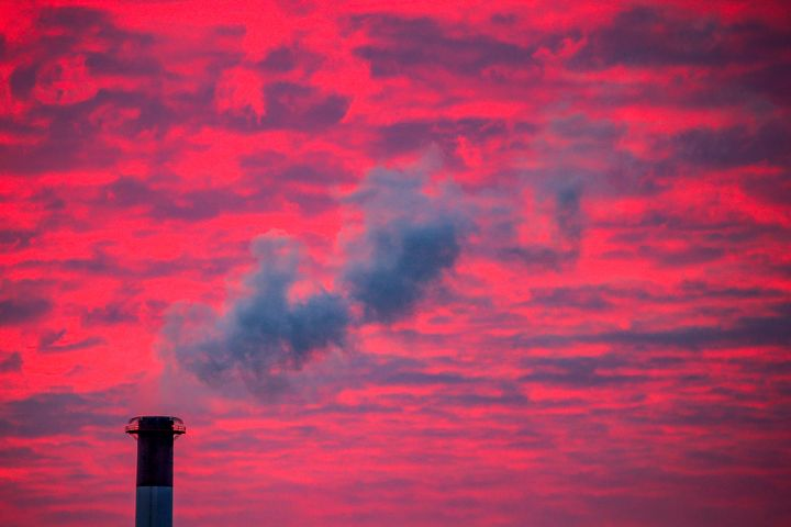 Steam rises from a smokestack at sunset in Lansing, Michigan.