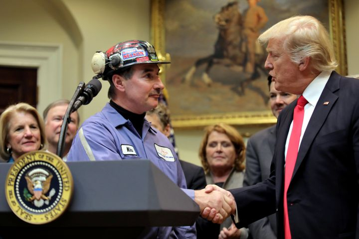 Coal miner Michael Nelson shakes hands with President Donald Trump as Trump prepares to sign Resolution 38, which nullifies t