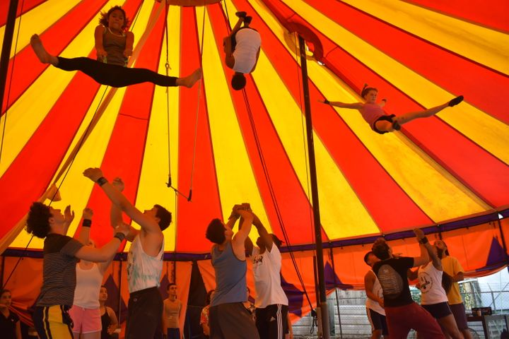 Students fly in the air during a trick in the tent in Dorado.