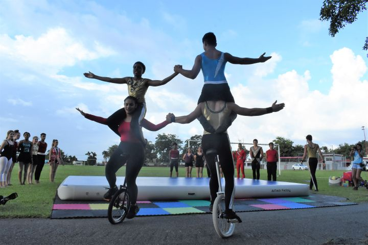 Students Ilka Miranda, Ari Maayan, Malik Leeks, and Finn McNamee perform a unicycle trick in Yabucoa.