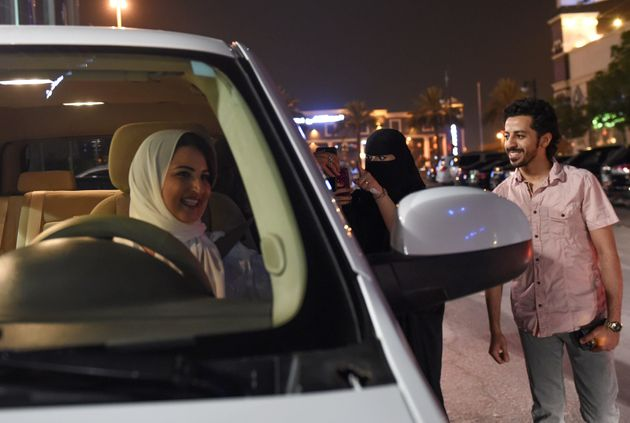 A Saudi woman films and shows support to Samar Almogren (left), who drives her car through the streets...