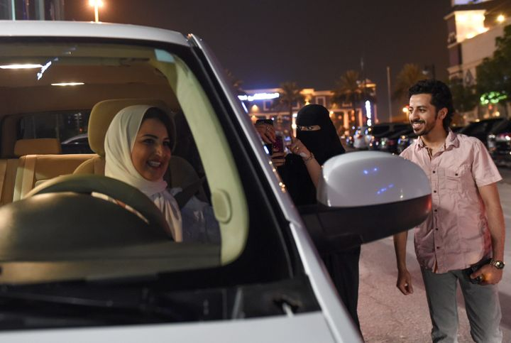 A Saudi woman films and shows support to Samar Almogren (left), who drives her car through the streets of the Saudi capital Riyadh for the first time just after midnight, June 24, 2018, when the law allowing women to drive took effect.