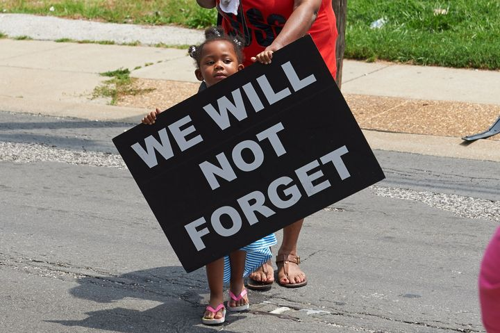 A young girl holds a sign on Aug. 8, 2015, in Ferguson, Missouri, a year after the police shooting death of Michael Brown Jr.