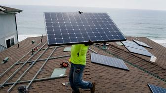 Andres Quiroz, an installer for Stellar Solar, carries a solar panel during installation at a home in Encinitas, California, U.S., on Wednesday, Aug. 15, 2012. Stellar Solar installs residential and commercial solar panels in the San Diego area. Photographer: Sam Hodgson/Bloomberg via Getty Images