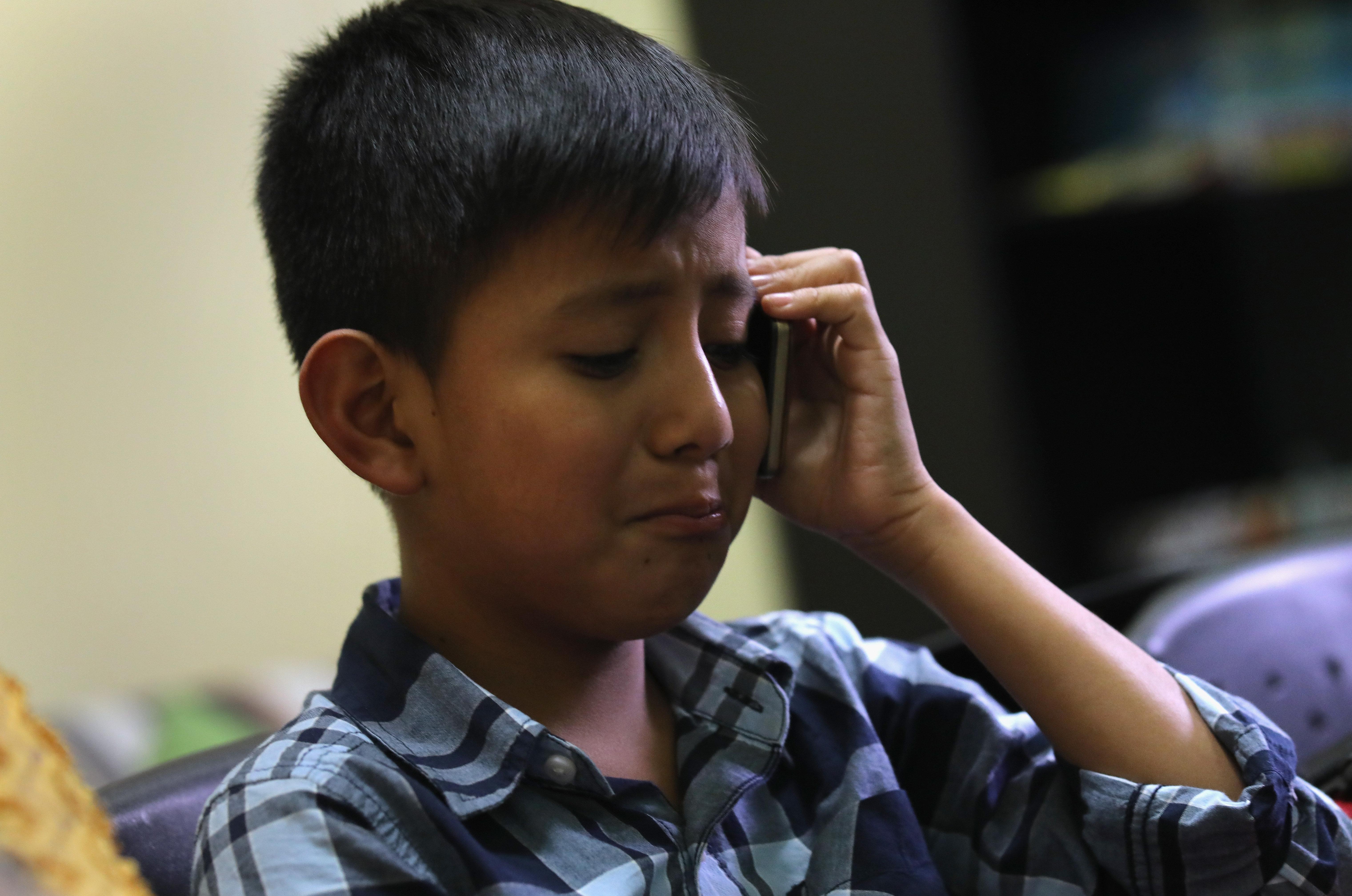 Un niño de 10 años habla con su madre por teléfono después de reunirse con su padre en el centro de inmigrantes...