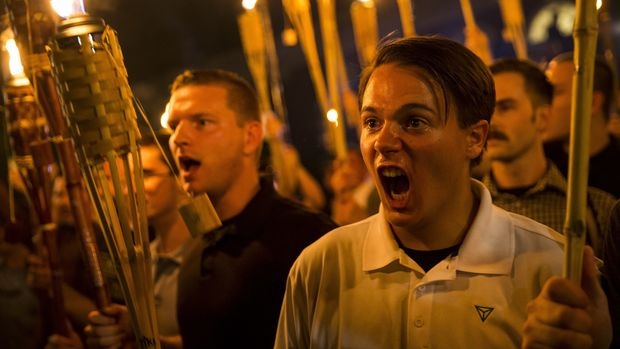 CHARLOTTESVILLE, USA - AUGUST 11: Peter Cvjetanovic (R) along with Neo Nazis, Alt-Right, and White Supremacists encircle and chant at counter protestors at the base of a statue of Thomas Jefferson after marching through the University of Virginia campus with torches in Charlottesville, Va., USA on August 11, 2017. (Photo by Samuel Corum/Anadolu Agency/Getty Images)