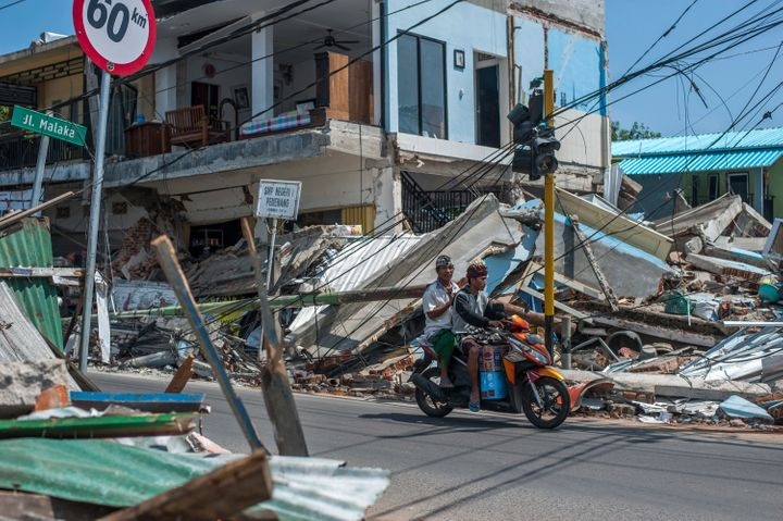 Motorists ride past buildings ruined by Sunday's earthquake in Pamenang, Lombok Island, Indonesia, Friday, Aug. 10, 2018. The