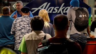 Air Alaska passengers wait in the terminal following an incident where an airline employee took off in an airplane, at Seattle-Tacoma International Airport in Seattle, Washington, U.S., August 10, 2018. REUTERS/Brendan McDermid