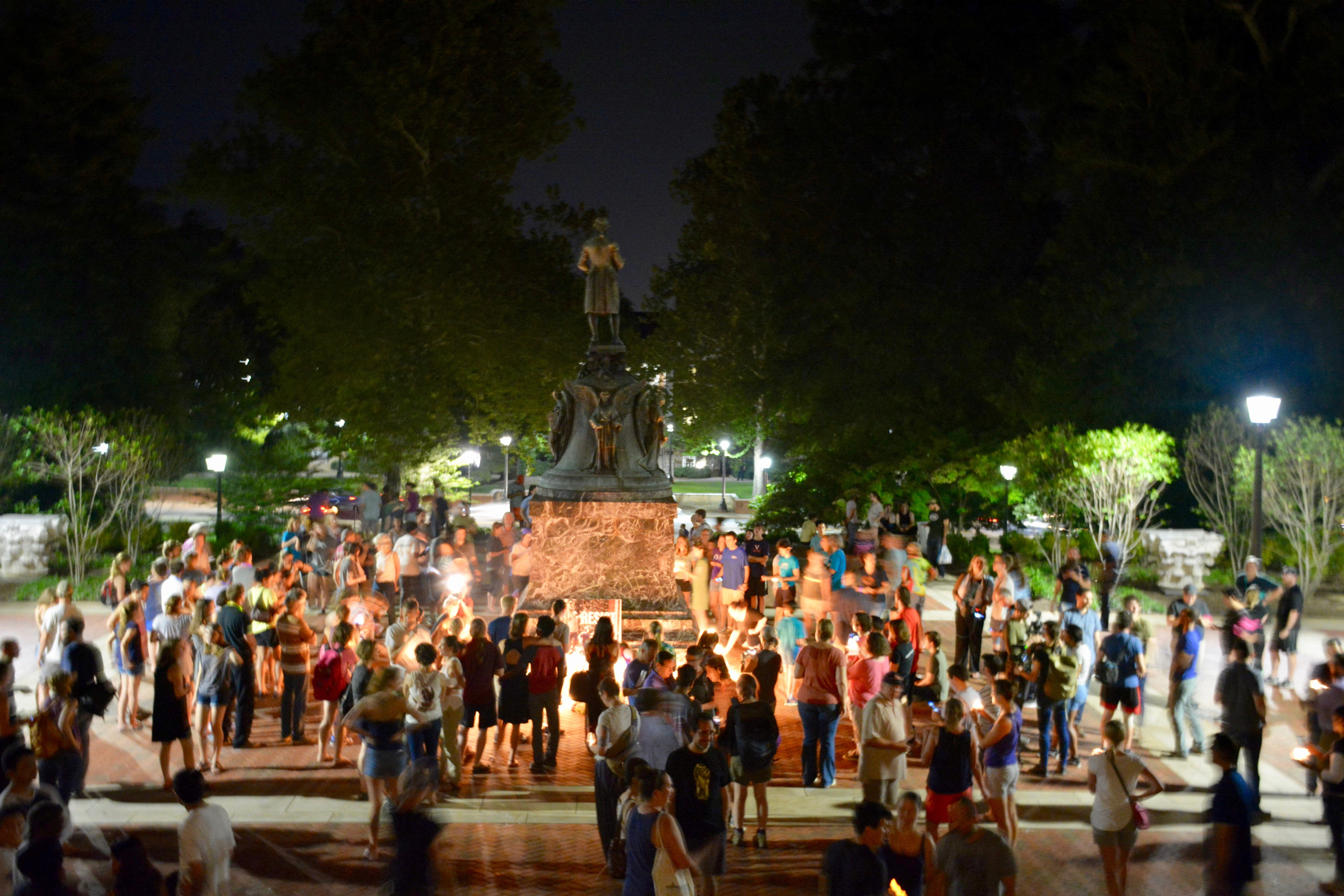 Charlottesville community members leave candles and flowers at the base of a statue of Thomas Jefferson north of University of Virginia's Rotunda at a vigil for Heather Heyer following last Saturday's protest organized by white nationalists that turned deadly in Charlottesville, Virginia, U.S. on August 16, 2017. Picture taken on August 16, 2017.   Courtesy Tim Dodson/The Cavalier Daily/Handout via REUTERS   ATTENTION EDITORS - THIS IMAGE WAS PROVIDED BY A THIRD PARTY. MANDATORY CREDIT.