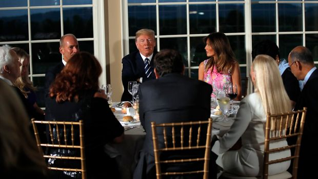 President Donald Trump sits with first lady Melania Trump as he meets with business leaders, Tuesday, Aug. 7, 2018, at Trump National Golf Club in Bedminster, N.J. (AP Photo/Carolyn Kaster)