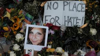 """A photograph of Charlottesville victim Heather Heyer is seen amongst flowers left at the scene of the car attack on a group of counter-protesters that took her life  during the """"Unite the Right"""" rally as people continue to react to the weekend violence in Charlottesville, Virginia, August 14, 2017.  REUTERS/Justin Ide"""