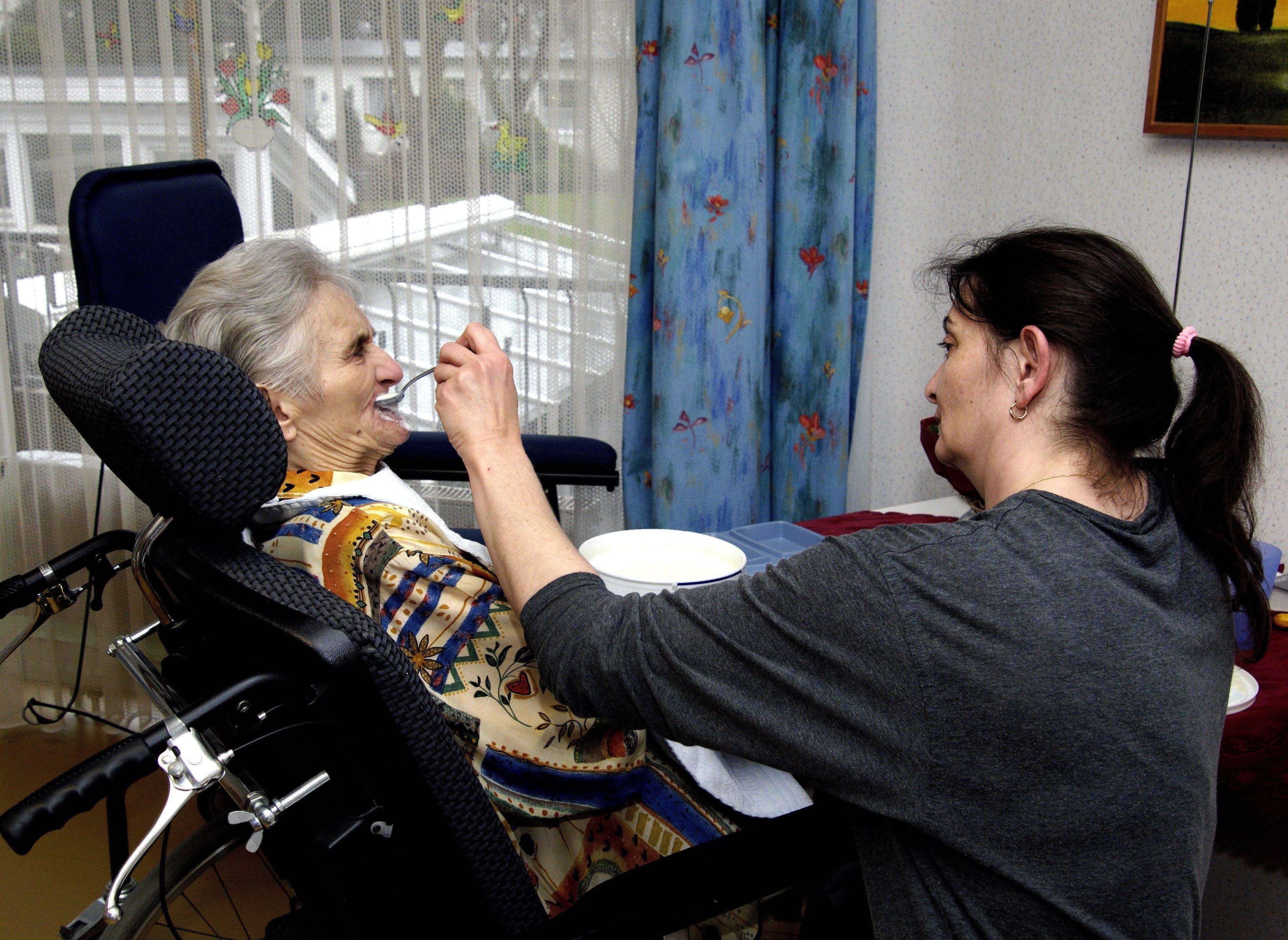 Eine Pflegerin reicht einer alten Frau das Frühstück in einem Pflegeheim
