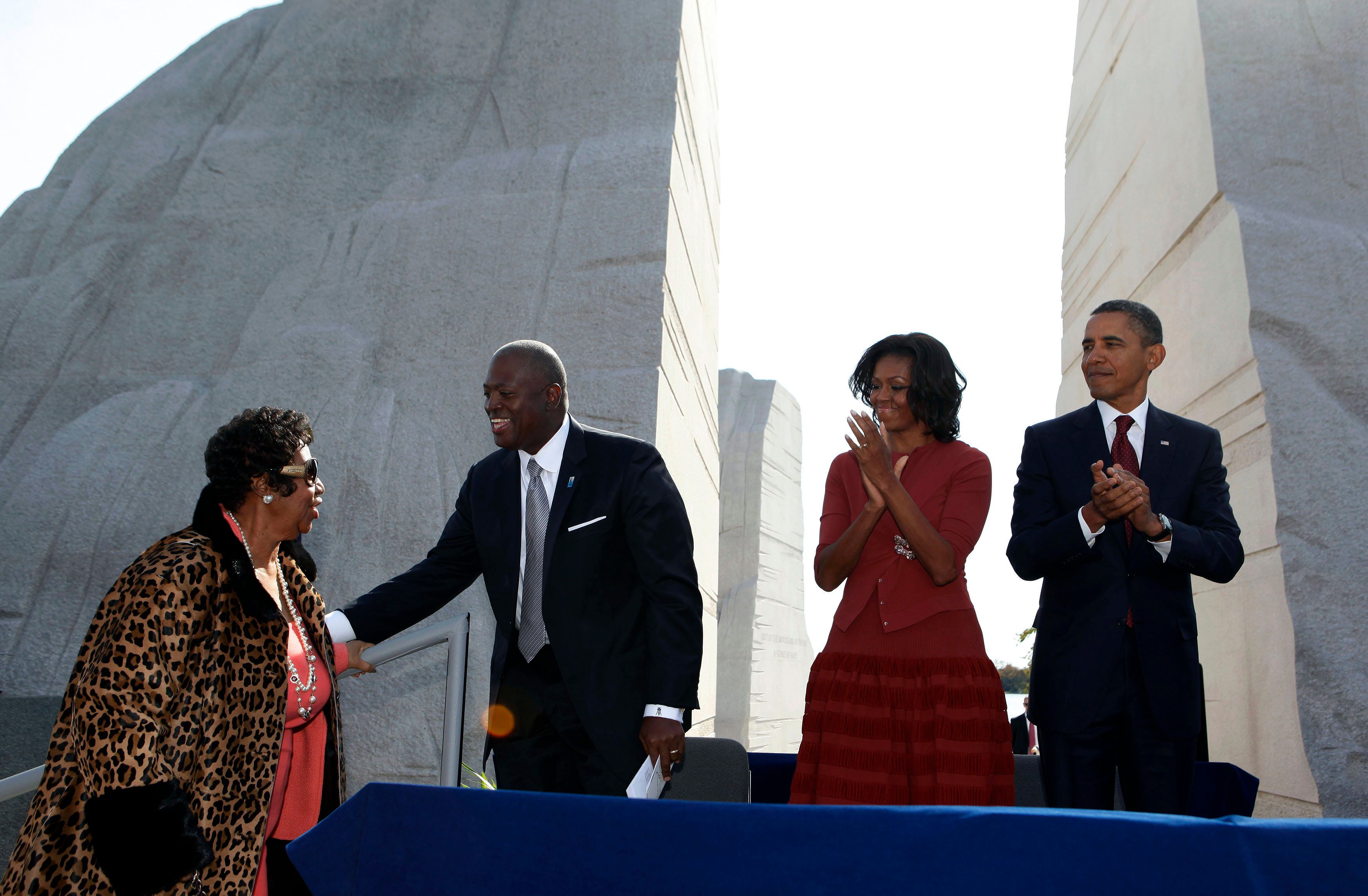 U.S. President Barack Obama (R) next to first lady Michelle Obama (2nd R) and CEO of the Martin Luther King, Jr. National Memorial Foundation Harry E. Johnson (2nd L) welcome singer Aretha Franklin (L) on stage before she sings at the dedication ceremony of the Martin Luther King, Jr. Memorial in West Potomac Park in Washington, October 16, 2011.         REUTERS/Larry Downing     (UNITED STATES - Tags: POLITICS ENTERTAINMENT)