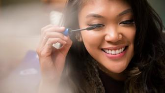 Mixed Race woman applying mascara