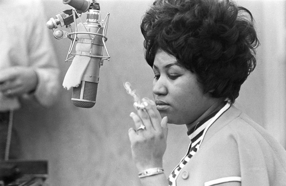 Smoking a cigarette as she works in the studio by a microphone at Muscle Shoals Studios in 1969 in Muscle Shoals, Alabam