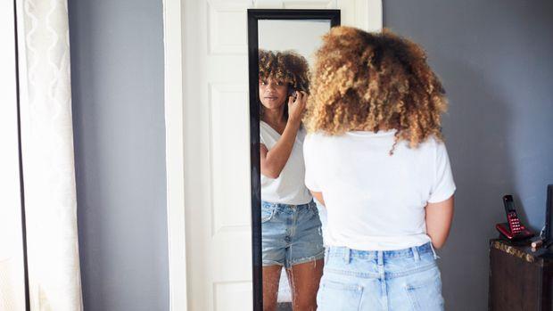 Black woman examining hair in mirror