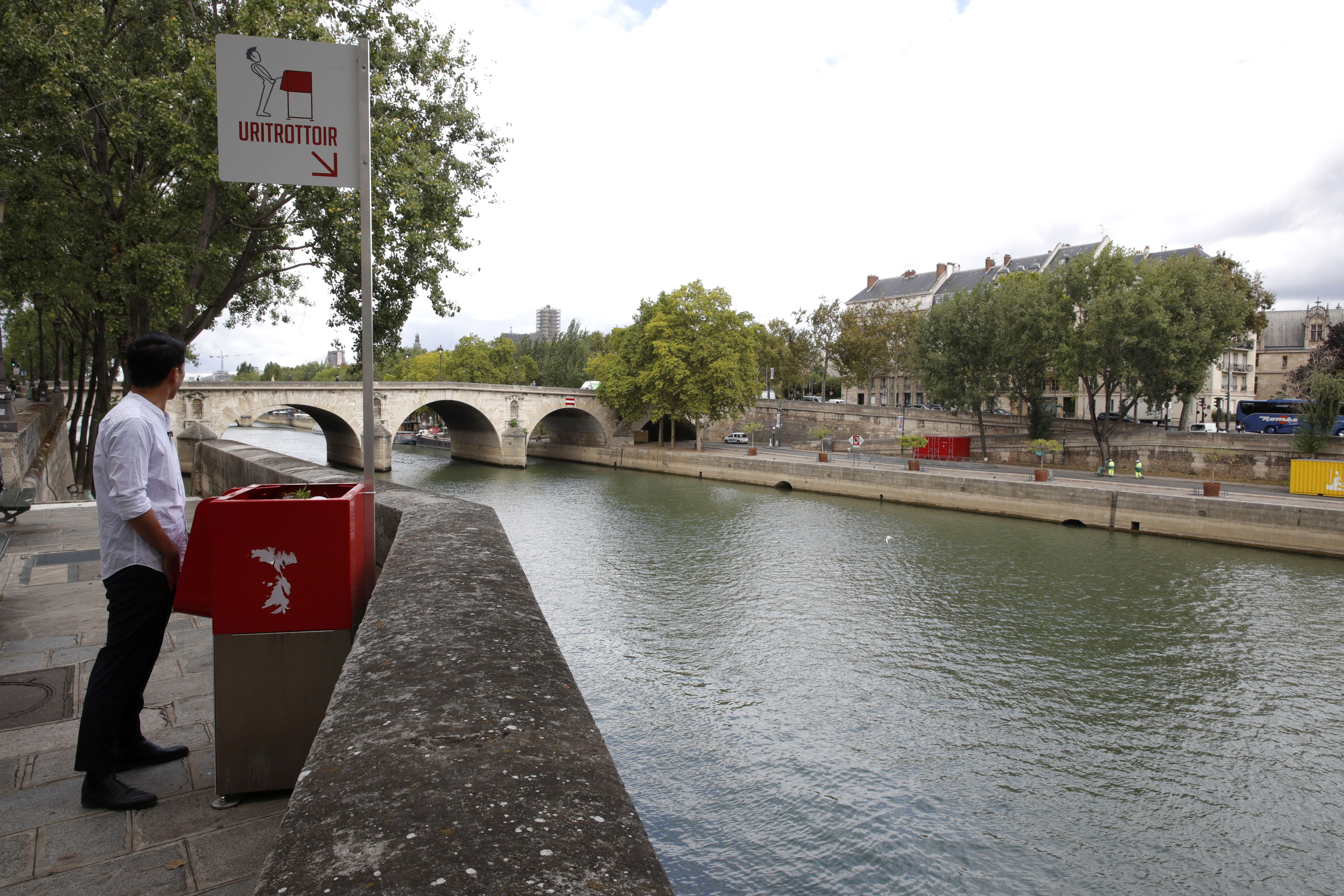A journalist poses as he stands in front of a bright red, eco-friendly urinal on the Ile Saint-Louis along the Seine River in Paris, France, August 13, 2018.  REUTERS/Philippe Wojazer
