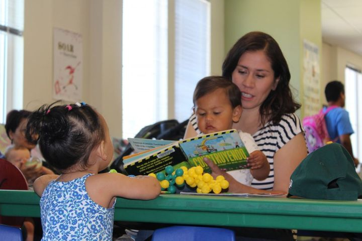 Mother, Elizabeth Paniagua, reads a board book with her 20-month-old son Joaquin, at Cesar Chavez Public Library located in the Fruitvale neighborhood in Oakland, California.