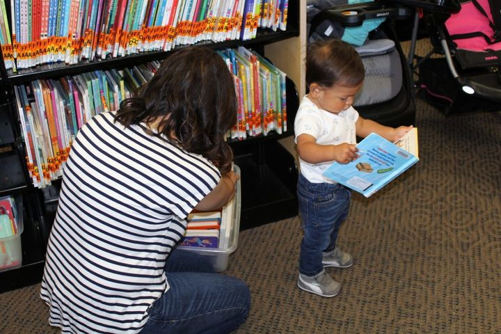 <p>Elizabeth Paniagua and her son Joaquin look for new books to check out from the local library. Cesar Chavez Public Library in Oakland Calif., also provides parents with toys as a checkout option.</p>