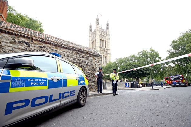 Police stand at the cordon in place near theHouses of Parliament, Westminster in central